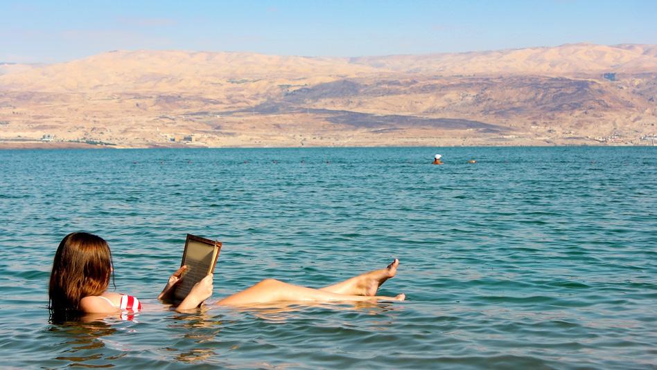 צעירה קוראת ספר בשעה שהיא צפה במימי ים המלח. צילום  Depositphotos